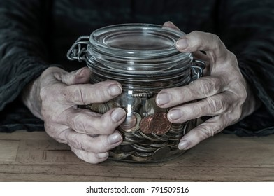 Hands of an old woman holding a mason jar with coins./Hands hold a mason jar with small change