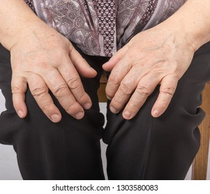 Hands of an old woman lying on her lap.