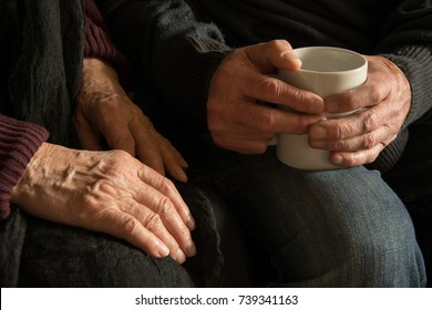 Hands of an old woman and an old man holding a mug