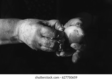 Hands of old woman piling a boiled potato. Black and white photography.