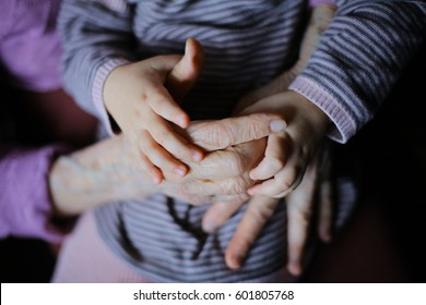 Hands of the old woman and small child grandmather and granddaughter. Concept of unity, support, protection, happiness and care. Grandparents holding wrists together closeup playing handplay anonymous