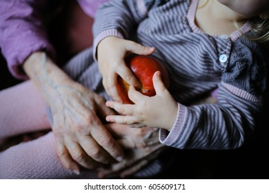 Hands of the old woman and small child grandmather and granddaughter. Concept of unity, support, protection, happiness and care. Grandparents holding wrists together closeup with play apple anonymous