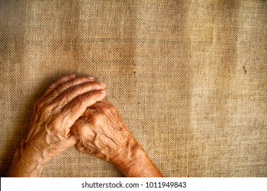 Hands of old woman who work hard like a labor for all her life/ isolated wrinkle hand on the sack background, vintage style