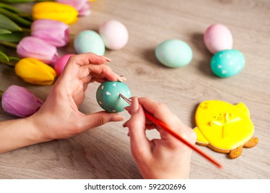 Hands on background wooden table girl paints the Easter eggs, preparing for the holiday, decor