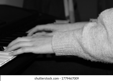 hands on a black and white piano