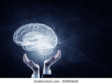 Hands on dark background holding with care brain glowing symbol