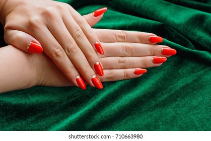 Hands on green velvet with red manicure and gold holes. The concept of beauty and hand care. Female tricks and charms. Vintage manicure