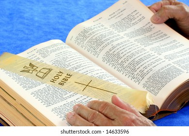 Hands on Holy Bible giving the effect of someone reading.