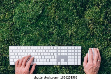 Hands on laptop keyboard over green grass, moss forest background. Top view. Mindfulness, biophilic design, unplug concept. Digital detox. Summer office, work on vacation, freelance concept.