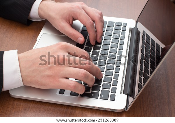 Hands on the laptop at the wooden table, closeup