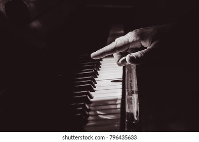 hands on piano, dark background
