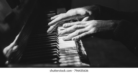 hands on piano, dark background