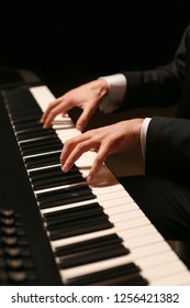 Hands on piano. The pianist plays the piano. Piano keys on black background
