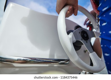 Hands on a steering wheel on a motor boat.Closeup.Sailor theme
