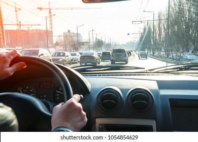 Hands on the steering wheel. View of the road in the city through the windshield of the car