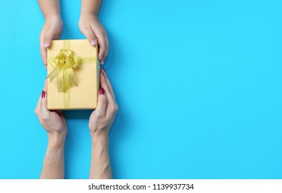 Hands on the table box gift giving congratulation blue background