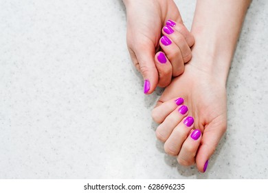 Hands on the table with manicure.Nails purple, pink.