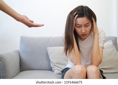 Hands on temples of young unhappy sadness Asian girl sitting on sofa. Her boyfriend is consoling her by giving his hand to her. Seen from the front. Stressful and consolation concept.