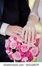 hands on a wedding bouquet showing wedding rings