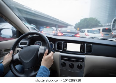 Hands on wheel driving car in traffic jam city