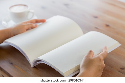 Hands open Blank catalog, magazines,book mock up on wood table with coffee