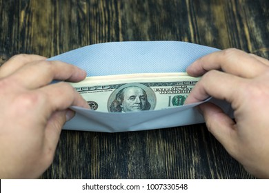 Hands open an envelope with money.