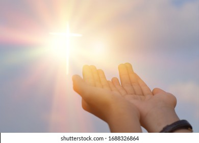 Hands open palm up worship over sunrise background. Catholic praying for blessing from god.