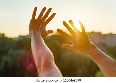 Hands open to the sunset, meditation, the background of the open window in the house, the silhouette of the city and the evening sun.