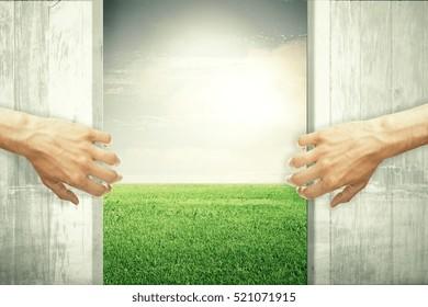 Hands opening abstract wooden doors, revealing green meadow view. Nature concept
