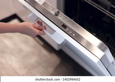 Woman'S Hands Opening Or Closing Dishwasher'S Door, Closeup And Selective Focus. Young Housewife Puts Dirty Dishes In Dishwasher, Caring About House, Doing Housework, Run Dishwasher Machine.