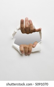 hands opening a hole in white cardboard