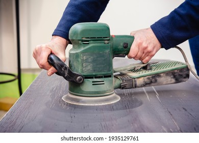 Hands with orbital electric sander on a wooden table