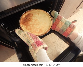 hands in oven gloves take tart from an oven. Also in Monochrome.