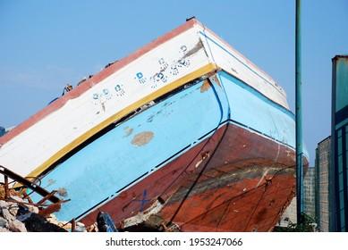 Hands over a broken boat in Lampedusa. Summer 2009.