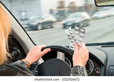 Hands with packs of tablets at the steering wheel of a car while driving