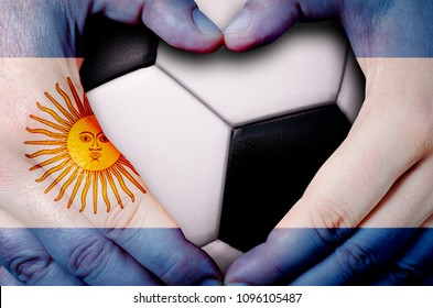 Hands painted with an Argentina flag forming a heart over soccer ball background
