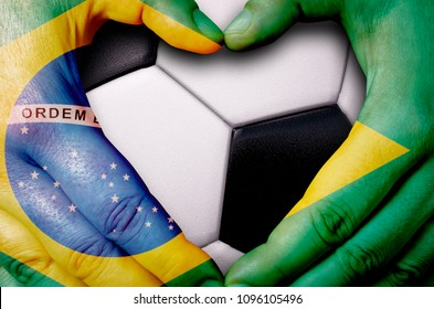 Hands painted with a Brazil flag forming a heart over soccer ball background