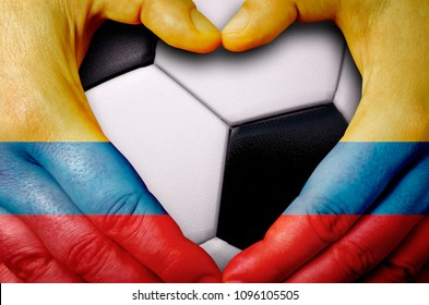 Hands painted with a Colombia flag forming a heart over soccer ball background
