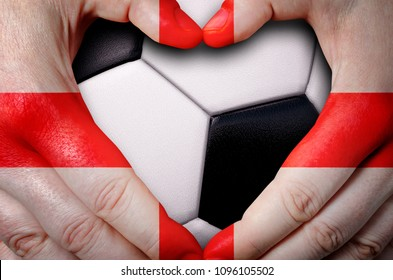 Hands painted with an England flag forming a heart over soccer ball background