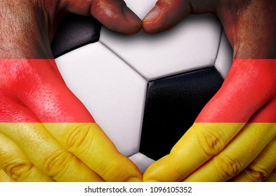 Hands painted with a Germany flag forming a heart over soccer ball background