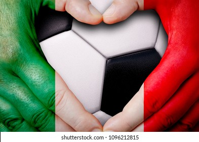 Hands painted with a Mexico flag forming a heart over soccer ball background