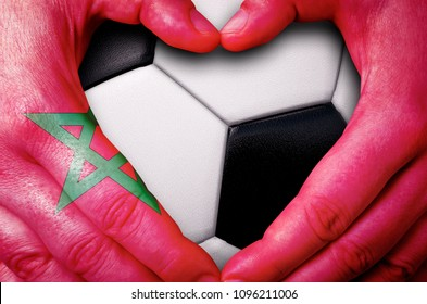 Hands painted with a Moroccan flag forming a heart over soccer ball background