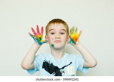 Hands painted with paint at the boy, smiling