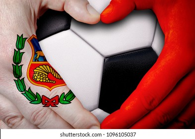 Hands painted with an Peru flag forming a heart over soccer ball background