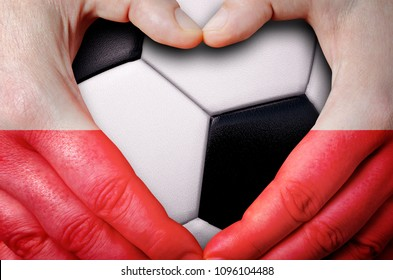 Hands painted with a Poland flag forming a heart over soccer ball background