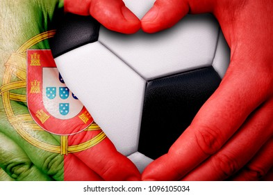 Hands painted with a Portugal flag forming a heart over soccer ball background