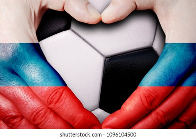 Hands painted with a Russia flag forming a heart over soccer ball background
