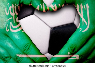 Hands painted with a Saudi Arabia flag forming a heart over soccer ball background