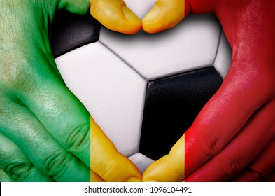 Hands painted with a Senegal flag forming a heart over soccer ball background