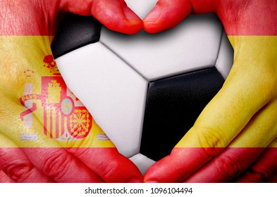 Hands painted with a Spain flag forming a heart over soccer ball background